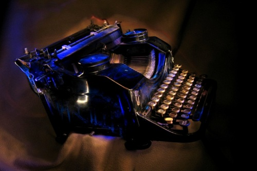 Antique black typewriter painted with UV light. Various objects on a dark background. Artistic blur.